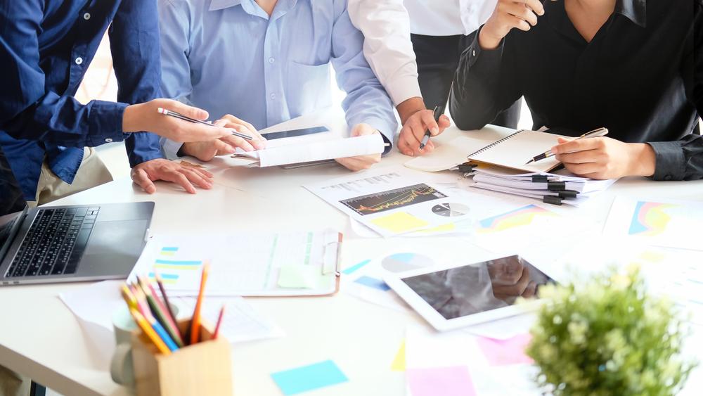 equipo reunido en una mesa de oficina para definir la estrategia de un negocio